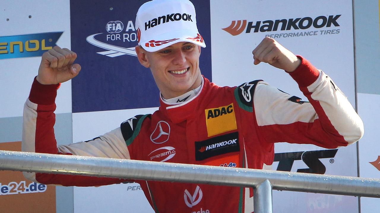 Mick Schumacher celebrates after winning the FIA Formula Three European Championship at the Hockenheim race track in Hockenheim, western Germany, on October 14, 2018. - His first F3 title means Mick Schumacher has qualified for a FIA 'super licence', a prerequisite for the jump to Formula One, and follows on from his father Michael Schumacher, who won the German F3 championships 28 years ago. (Photo by Daniel ROLAND / AFP)