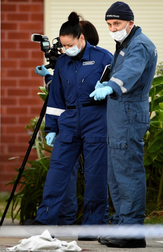 Police examine a possible clue to the woman's death. Picture: Nicole Garmston