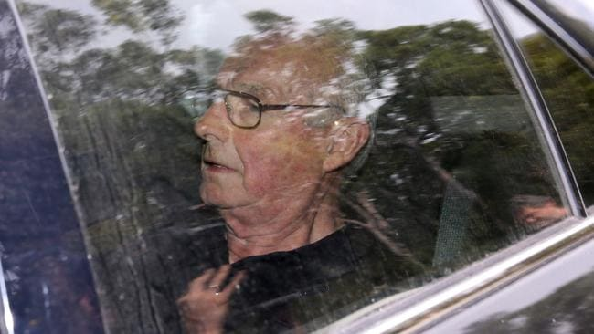 Taken away ... Rogerson is driven from his home by detectives. Picture: John Grainger
