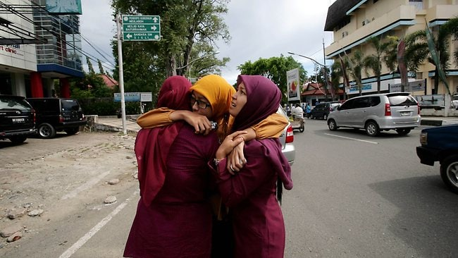 Acehnese women hug each other and pray shortly after the powerfull earthquake hit. Picture: AFP