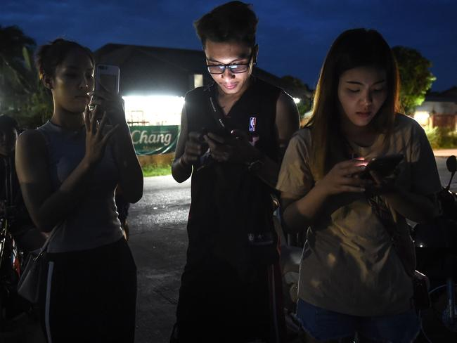 People anxiously check their mobile phones for updates while waiting at a military air base during the emergency helicopter evacuation to a hospital in Chiang rai. Picture: AFP Photo / Lillian Suwanrumpha