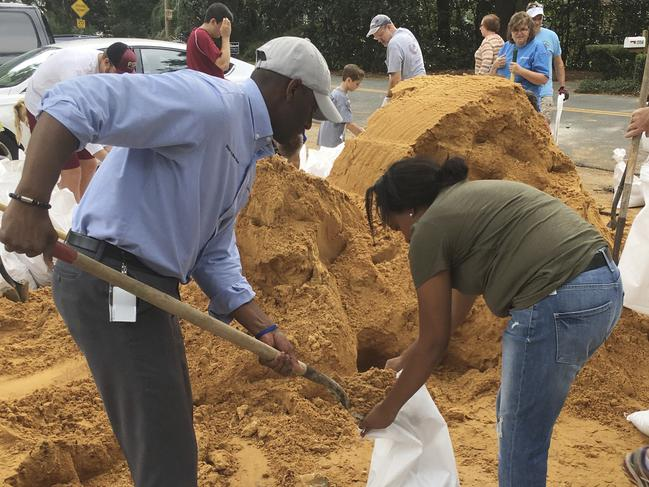 Tallahassee Mayor and Democratic gubernatorial candidate, Andrew Gillum, left, helps Eboni Sipling fill up sandbags in Tallahassee, Florida. Picture: AP