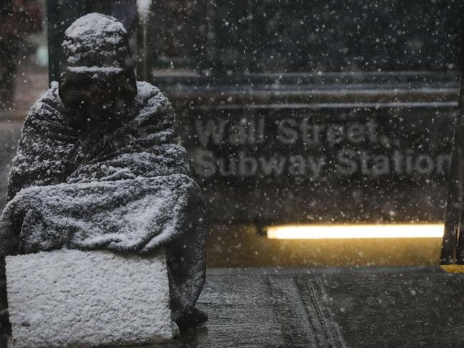 A homeless man sits in the falling snow in the Financial District in New York City. Picture: Getty