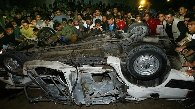 Palestinians chant and gather around the car of Hamas leader in Gaza Dr. Abdel Aziz Rantisi following an Israeli missle strike in Gaza City, Saturday on April 17, 2004. Rantisi died later of his wounds, according to hospital officials. Picture: AP /Kevin Frayer