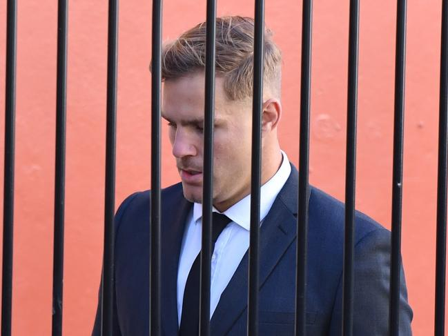 St. George Illawarra Dragons player Jack de Belin is seen walking behind a fence as he arrives at Wollongong Local Court on Tuesday (AAP Image/Dean Lewins)