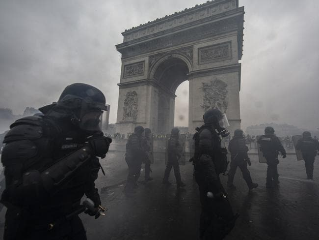 Tear gas surrounds riot police as they clash with protesters during a 'Yellow Vest' demonstration near the Arc de Triomphe. Picture: Getty