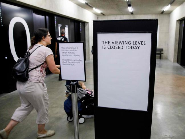 Visitors walk by a sign that explains that the viewing level is closed in the Tate Modern following the incident on Sunday. Picture: AFP