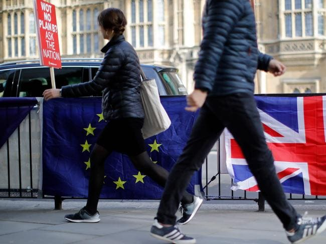Pedestrians walk past the banners and flags of Anti-Brexit protesters outside the Houses of Parliament in London. Picture: AFP