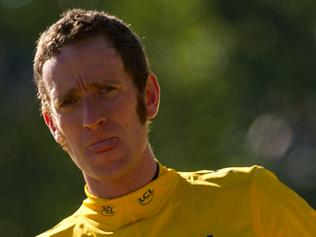 """(FILES) In this file photo taken on July 22, 2012 overall leader's yellow jersey and British Bradley Wiggins, celebrates on the podium at the end of the 120 km and last stage of the 2012 Tour de France cycling race starting in Rambouillet and finishing in the famous Paris-Champs-Elysees Avenue.   British cycling great Bradley Wiggins said it was """"so sad"""" after he and his former team were accused by MPs of manipulating drug rules before major races, including Wiggins' 2012 Tour de France victory on March 5, 2018. / AFP PHOTO / Lionel BONAVENTURE"""