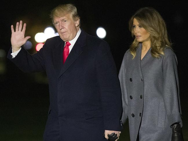 President Donald Trump waves as he walks with first lady Melania Trump, after stepping off Marine One, on the South Lawn of the White House on Sunday. Picture: AP Photo/Alex Brandon