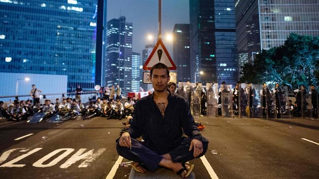 A protester sits at the middle of Harcourt Road in Hong Kong after a protest against a controversial extradition law proposal in Hong Kong on June 12, 2019.