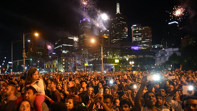 MELBOURNE, AUSTRALIA - DECEMBER 31: New Years revelers watching the fireworks on the Princes Bridge during New Years Eve fireworks on December 31, 2013 in Melbourne, Australia. (Photo by Vince Caligiuri/Getty Images)