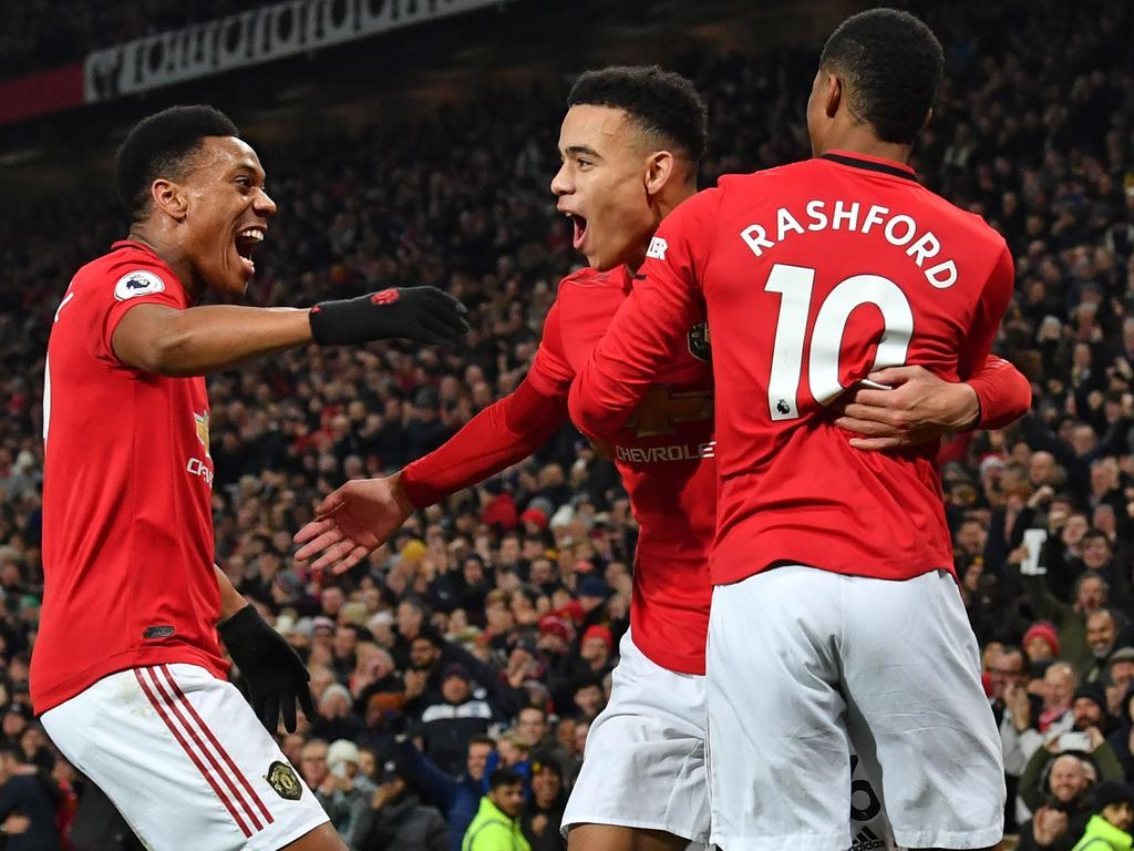 Manchester United's English striker Mason Greenwood (C) celebrates with Manchester United's French striker Anthony Martial (L) and Manchester United's English striker Marcus Rashford (R) after scoring their second goal during the English Premier League football match between Manchester United and Newcastle United at Old Trafford in Manchester, north west England, on December 26, 2019. (Photo by Paul ELLIS / AFP) / RESTRICTED TO EDITORIAL USE. No use with unauthorized audio, video, data, fixture lists, club/league logos or 'live' services. Online in-match use limited to 120 images. An additional 40 images may be used in extra time. No video emulation. Social media in-match use limited to 120 images. An additional 40 images may be used in extra time. No use in betting publications, games or single club/league/player publications. /