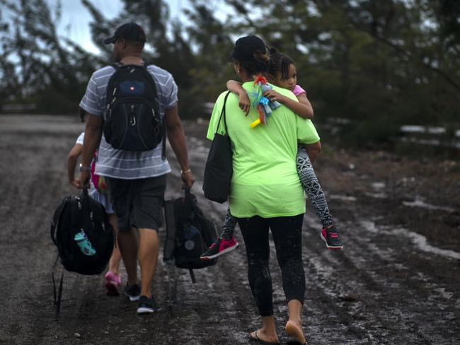 A family walks on a road after being rescued from the flood waters of Hurricane Dorian, near Freeport, Grand Bahama, Bahamas. Picture: AP