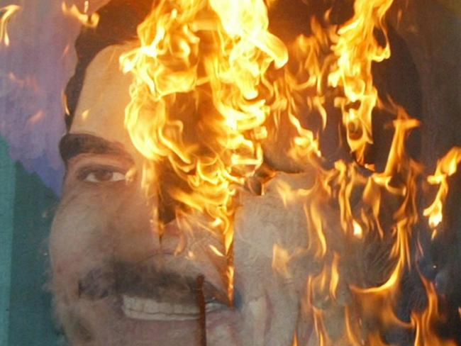 A poster of Iraqi President Saddam Hussein burning in Baghdad in April, 2003. Picture: AFP