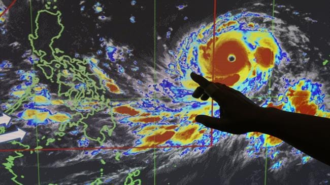 Filipino forecaster Meno Mendoza illustrates the path of Typhoon Mangkhut as it approaches the Philippines with sustained winds of 205kph and gusts of up to 285kph. Picture: Aaron Favila
