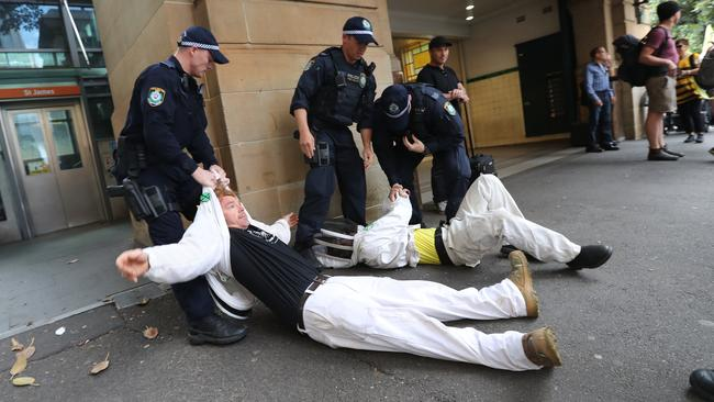 Police drag away protesters who laid down in the middle of traffic in Sydney on Tuesday. Picture: Richard Dobson