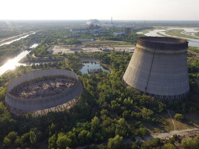 In this aerial view abandoned, partially completed cooling towers stand at the Chernobyl nuclear power plant as the new, giant enclosure that covers devastated reactor number four stands behind. Picture: Getty Images