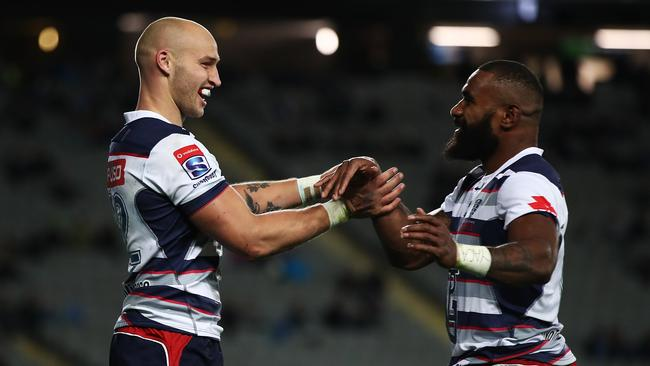 Billy Meakes and Marika Koroibete celebrate a Rebels try.
