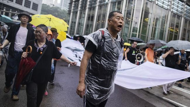 Jimmy Lai, center, holds a banner as he marches along Queen's Road Central during a protest in the Central district of Hong Kong. Picture: Getty Images