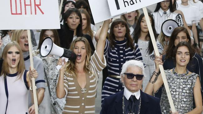 Gisele Bündchen walks the runway with Karl Largerfeld during a Chanel show.