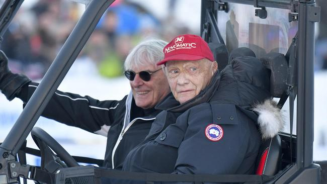 Lauda sporting his famous red cap, alongside Formula One supremo Bernie Ecclestone (L). Picture: AFP