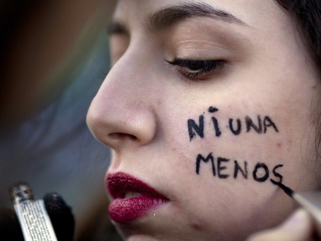 "A protester has the Spanish message ""not one less"" painted on her cheek during a pro-life demonstration in Buenos Aires. Picture: AP"