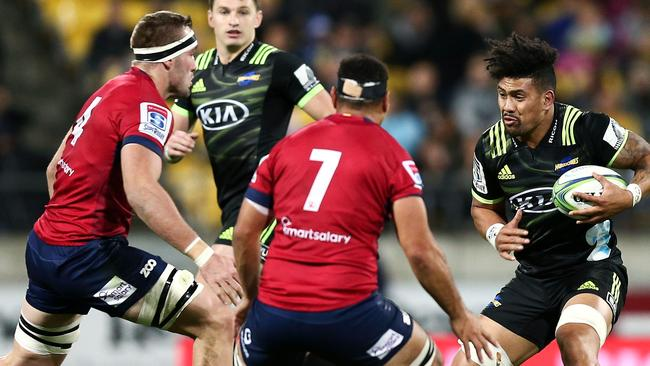 Ardie Savea of the Hurricanes runs at George Smith (right) and Izack Rodda of the Reds on Friday night.