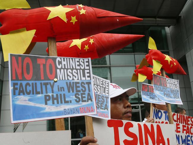 Environmental activists display mock missiles as they picket the Chinese Consulate to protest alleged military build-up by China on the disputed group of islands at the South China Sea, in the financial district of Makati east of Manila, Philippines. Picture: Bullit Marquez.