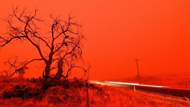 A long exposure picture shows a car commuting on a road as the sky turns red from smoke of the Snowy Valley bushfire on the outskirts of Cooma on Saturday. Picture: Saeed Khan / AFP