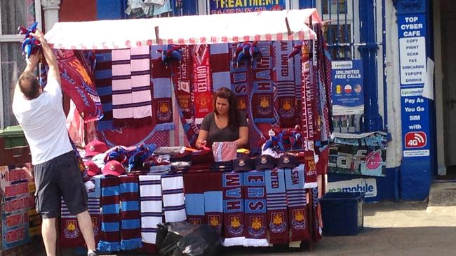A Green St souvenir stand prepares for the arriving crowd.