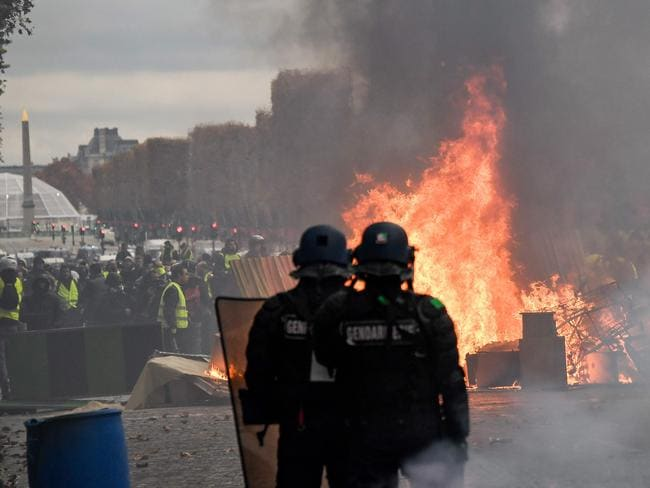 "Riot police face off against the ""yellow jacket"" demonstrators in front of a burning barricade in Paris. The violent altercations are the result of rising fuel costs. Picture: AFP"