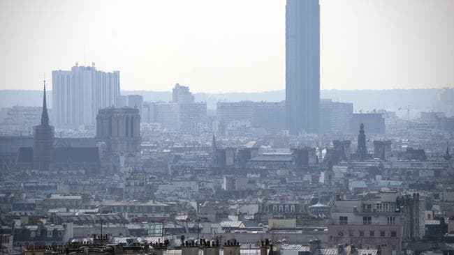 (FILES) This file picture dated March 27,2014 shows the Montparnasse Tower (R) and the Notre-Dame-de-Paris cathedral (L) in a thick smog. AFP/Lionel Bonaventure