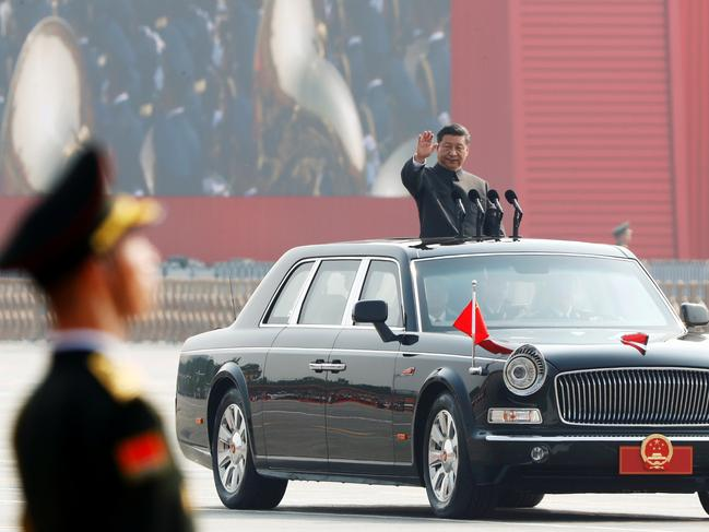 Chinese President Xi Jinping waves from a vehicle as he reviews troops at a military parade marking the 70th founding anniversary of People's Republic of China. Picture: Thomas Peter/ Reuters