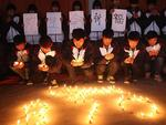 High school students hold candles during a vigil for passengers of the missing Malaysia Airline flight MH370 in Lianyungang, east China's Jiangsu province on March 25, 2014. Picture: AFP PHOTO CHINA OUT