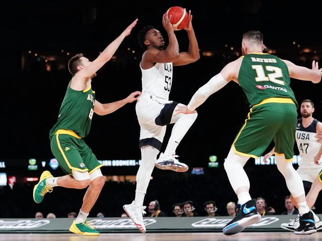 Donovan Mitchell of the USA rises for a floater between Matthew Dellavedova and Aron Baynes. Picture: Scott Barbour/AAP