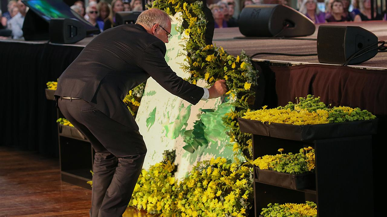 Prime Minister Scott Morrison places a flower on a map of Victoria at the 10th anniversary service in Melbourne. Picture: Ian Currie