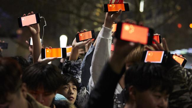 Pro-China counter protesters hold up phones showing the Chinese national flag. Picture: AAP Image/Erik Anderson