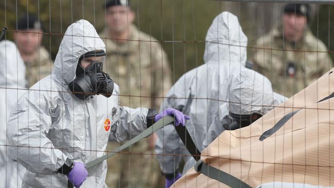 Military personnel wearing protective coveralls work to remove a vehicle connected to the nerve agent attack.
