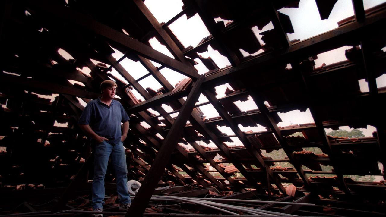 Sydney resident Greg Moore with his ruined attic roof after Australia's worst hailstorm in history in 1999.
