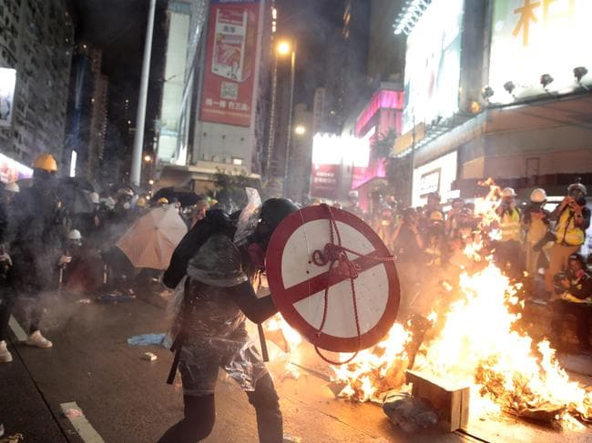 A protester uses a shield to cover himself as he faces policemen. Picture: Jae C Hong/AP