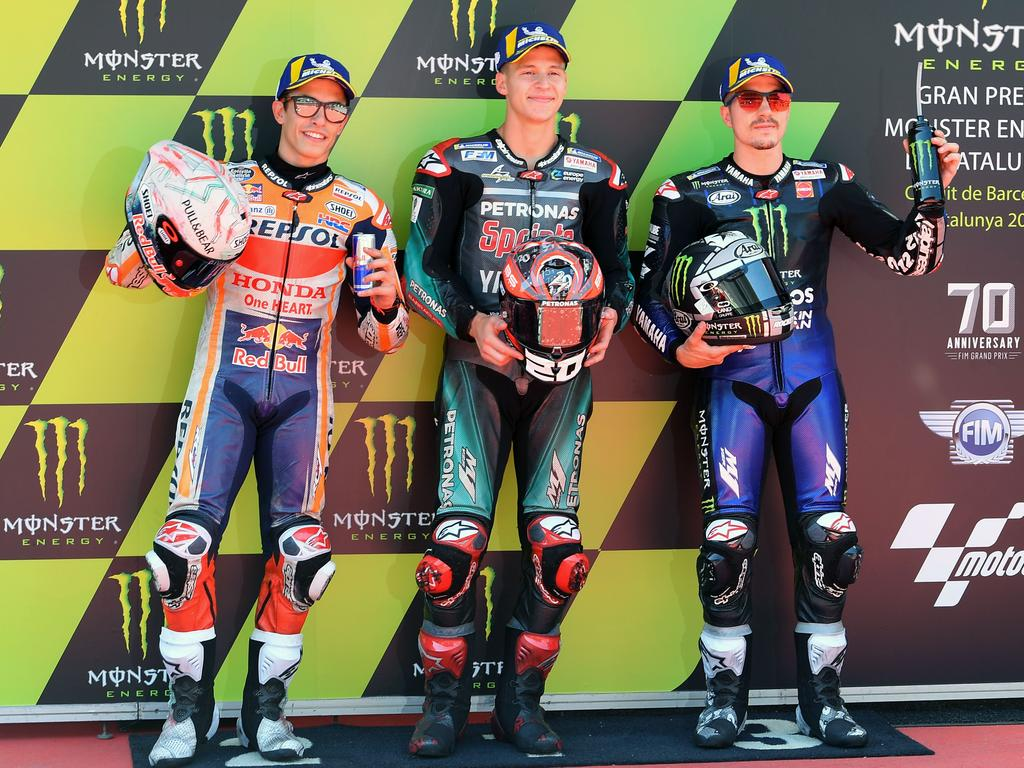 Repsol Honda Team's Spanish rider Marc Marquez (L), Petronas Yamaha SRT's French rider Fabio Quartararo (C) and Monster Energy Yamaha' Spanish rider Maverick Vinales (R) celebrate after the Catalunya MotoGP Grand Prix qualifying session at the Catalunya racetrack in Montmelo, near Barcelona, on June 15, 2019. (Photo by LLUIS GENE / AFP)