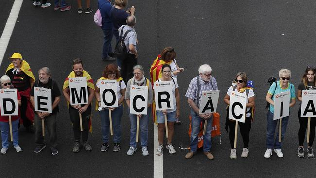 "Protesters march with a letters reading ""democracy"". Picture: AP"