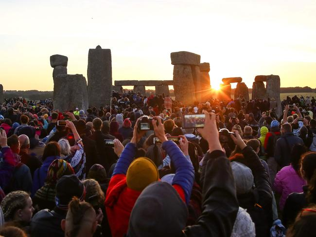 Revellers watch the sunrise as they celebrate the pagan festival of Summer Solstice at Stonehenge in Wiltshire, southern England on June 21, 2018. Picture: Geoff Caddick