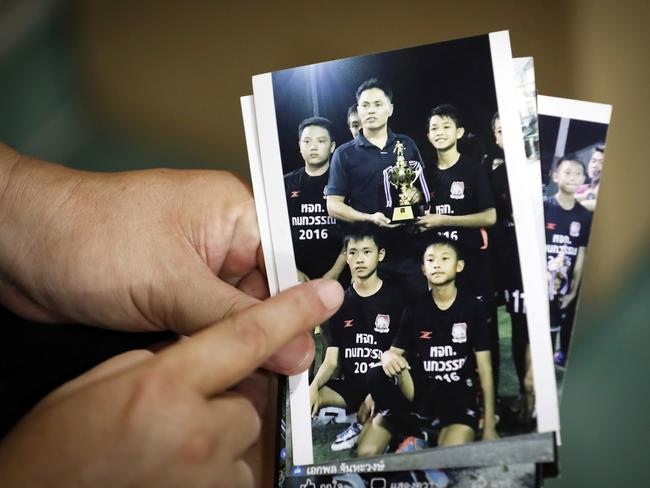 Banphot Konkum, father of Duangpetch Promthep, shows a picture of his son with his football team. Picture: AP/Vincent Thian