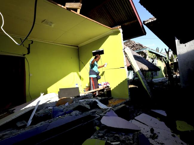 Items are salvaged from a home destroyed in an earthquake in North Lombok, Indonesia. Picture: Tatan Syuflana