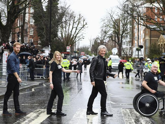 Britain's Prince Harry, Jon Bon Jovi and members of the Invictus Games Choir walk on the famous zebra crossing outside the Abbey Road Studios London. Picture: AP