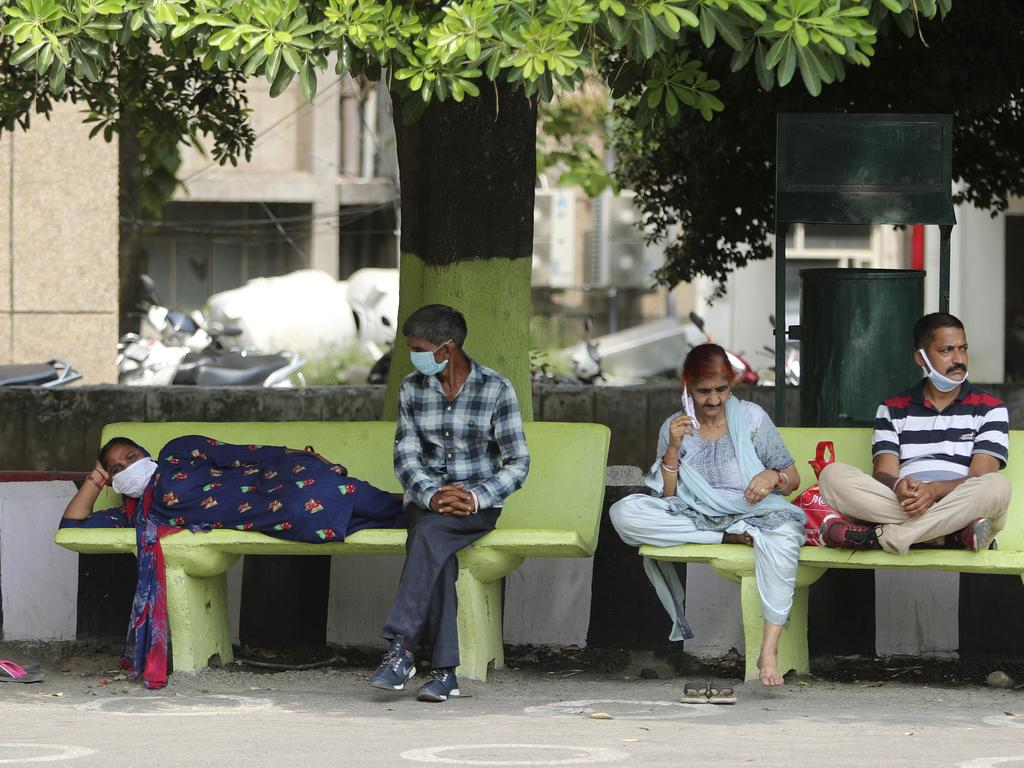 Indians rest outside a government run hospital in Jammu on Saturday. Picture: Channi Anand