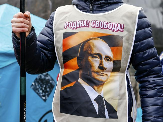 "Face of change ... A pro-Russia demonstrator wears a vest bearing a depiction of Russian President Vladimir Putin and the words, ""Motherland! Freedom!"" Picture: Andrey Basevich"