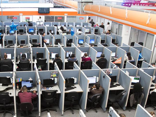 You should be reading up standing up ... Workers sit at desks at Firstkontact Centre, a call centre in the northern border city of Tijuana, Mexico, as the first advice of its kind recommends office workers stand for at least two hours a day. Picture: AP / Alex Cossio